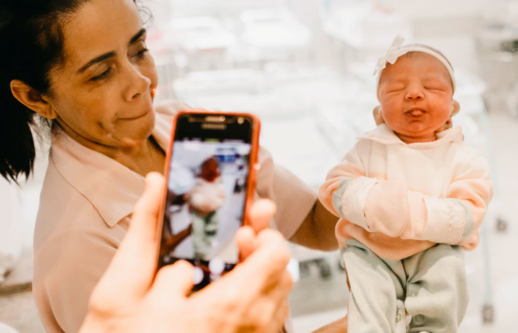couple taking photo of newborn in hospital with smartphone