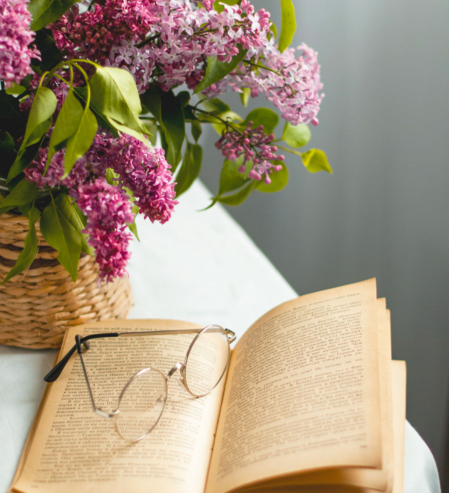 old book, spectacles, and lilacs