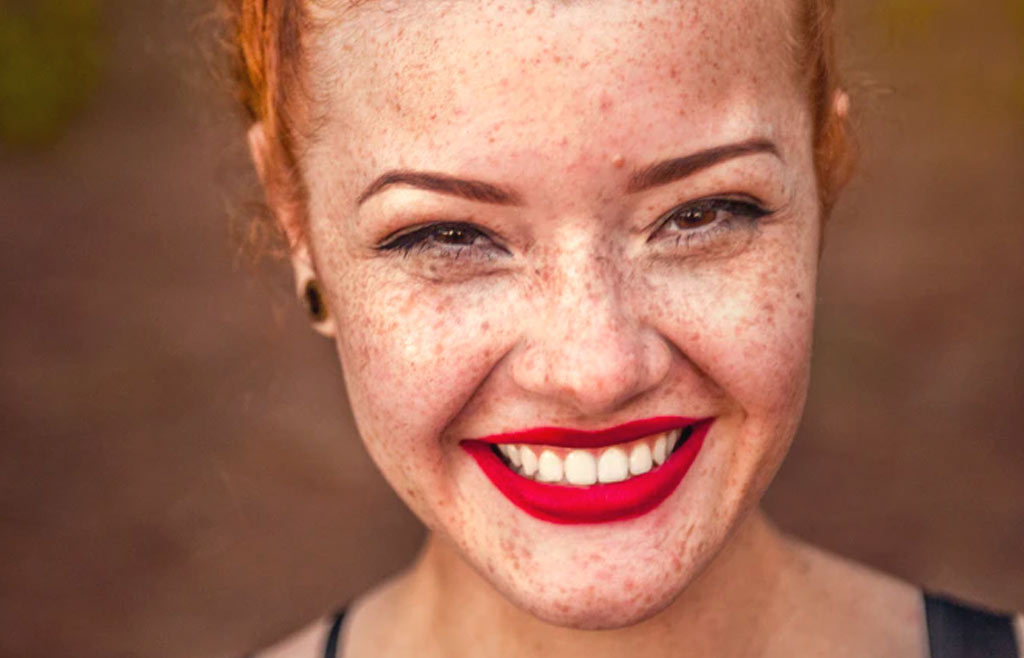 happy redhead girl with freckles