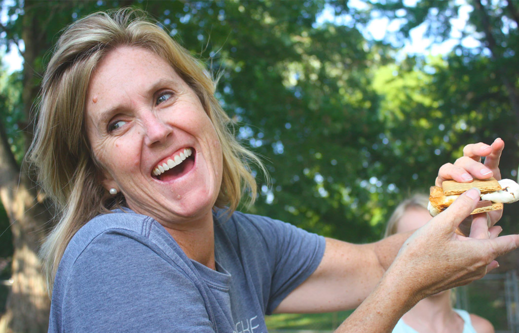 middle-aged woman laughing and holding a s'more
