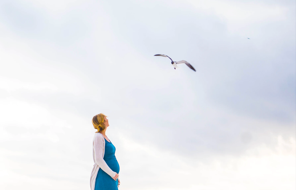 pregnant woman on beach looking at seagull
