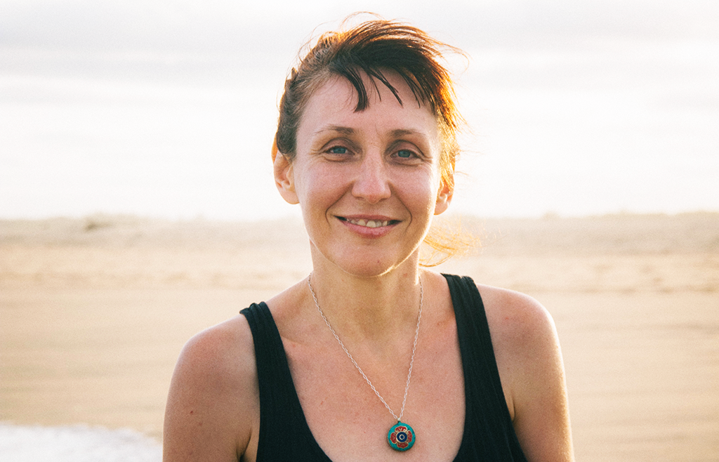 middle-aged woman smiling on beach